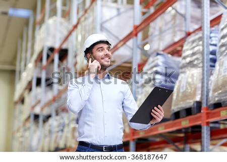 man with clipboard and smartphone at warehouse - stock photo