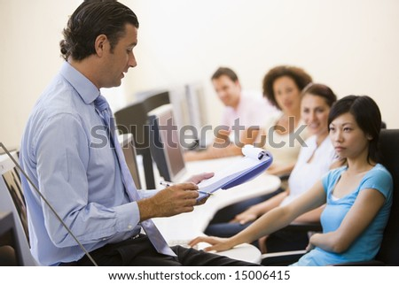 Man with clipboard giving lecture in computer class - stock photo