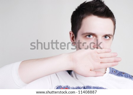 Man with closed mouth by hand - stock photo