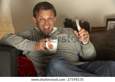 Man With Coffee Watching Television Excitedly - stock photo