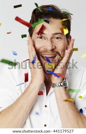 Man with confetti in studio, portrait - stock photo