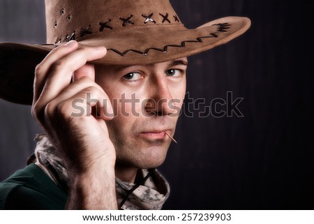 Man with cowboy hat and a toothpick - stock photo