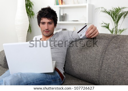 Man with credit card and computer - stock photo