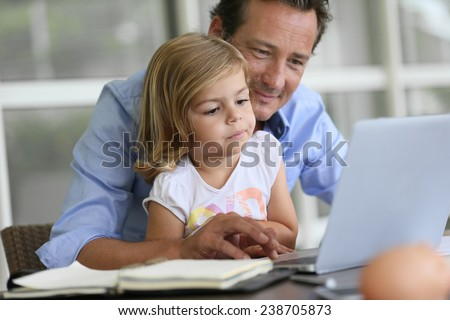 Man with daughter looking at internet on laptop - stock photo