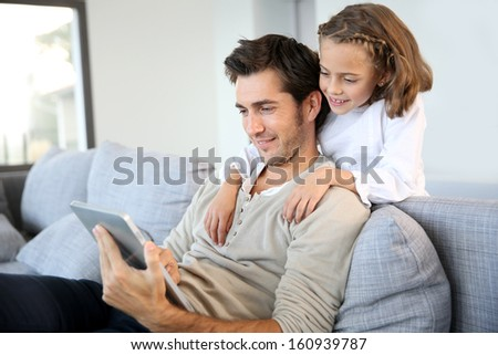 Man with daughter playing with digital tablet - stock photo