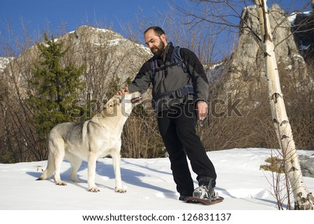 Man with dog hike in mountains - stock photo