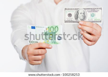 Man with dollar and euro banknote in hands - stock photo