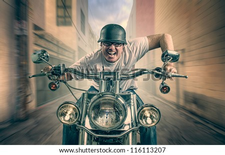 Man with earbuds on motorcycle - stock photo