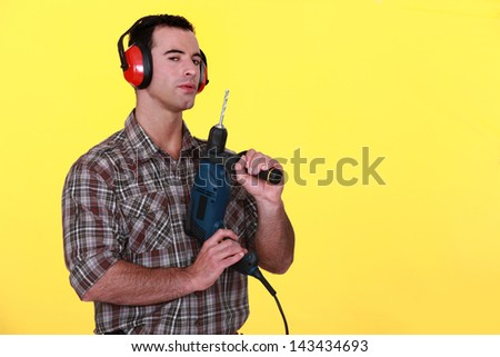 Man with earmuffs and drill - stock photo