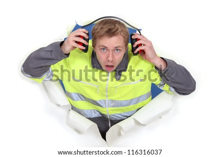 man with earmuffs emerging from poster - stock photo