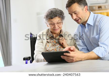 Man with elderly woman using digital tablet - stock photo