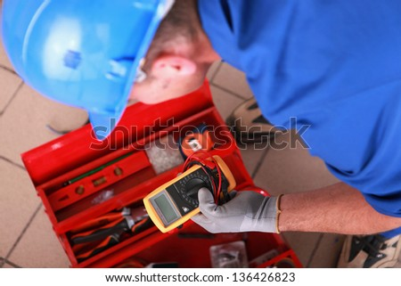 Man with electricity measurer - stock photo