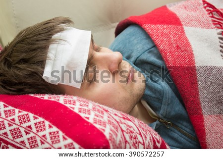 Man with fever sleeping on the sofa - stock photo