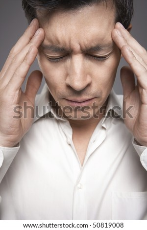 Man with fingers pressed to forehead, close-up - stock photo