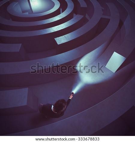 Man with flashlight in a dark maze - stock photo