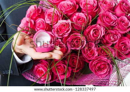 Man with flowers and ring in pink box. Proposal scene or Valentines day. - stock photo
