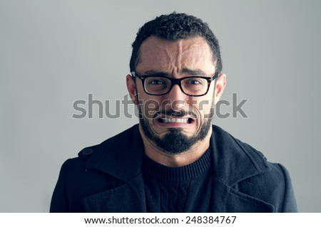 Man with Frustrated Expression isolated on grey background  - stock photo