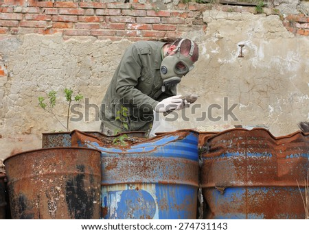 Man with gas mask and green military  clothes  explores  dead bird after chemical disaster.  - stock photo