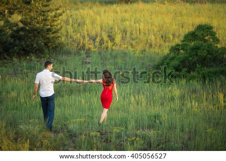 Man with girl on nature holding hands and walking away. Relationships - stock photo