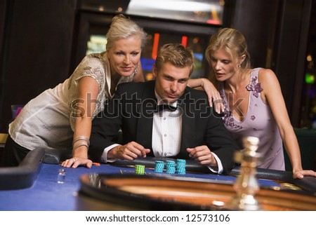 Man with glamorous women in casino at roulette table - stock photo