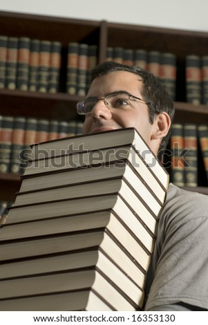 Man with glasses carries a stack of books through a library. Vertically framed photo. - stock photo