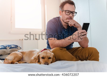 Man with glasses in blue shirt sitting on the bed with the dog and using smart phone. - stock photo
