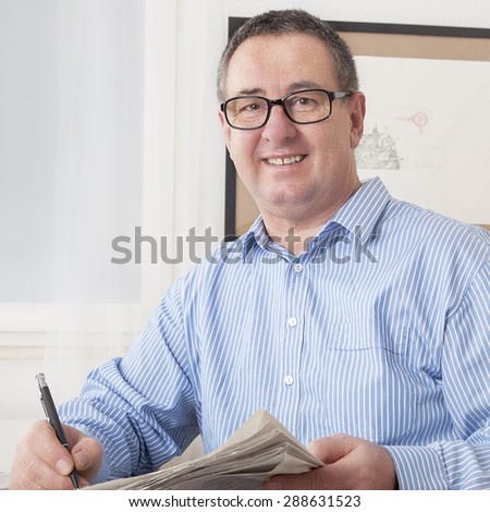 Man with glasses reading newspaper - stock photo