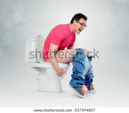 Man with glasses straining on the toilet. The concept of situation - stock photo