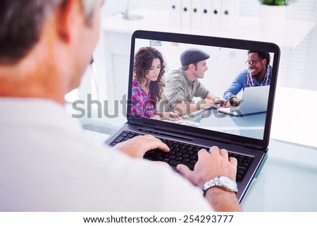 Man with grey hair typing on laptop against creative team working together - stock photo