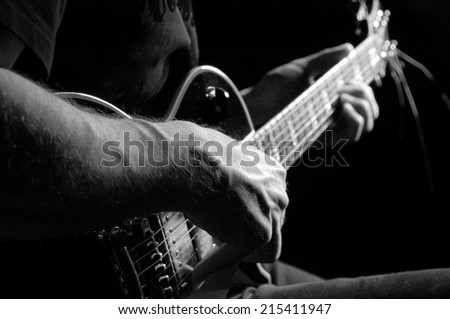 Man with guitar in a black T- shirt at the age of forty-six years old playing guitar on a black background - stock photo