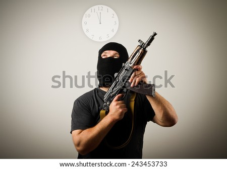 Man with gun looking at a clock. Time concept. - stock photo