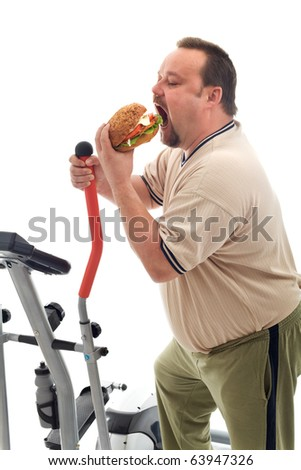 Man with gymnastic trainer device eating a large hamburger - isolated - stock photo