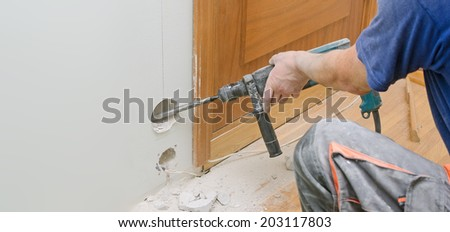 Man with Hammer drill doing hole for socket. Place for text. - stock photo