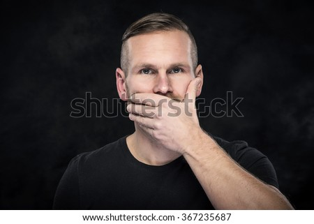 Man with hand covering his mouth on dark background. - stock photo