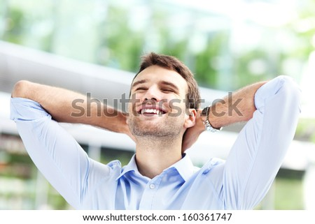 Man with hands behind his head, relaxing - stock photo