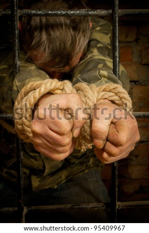 Man with hands tied with rope behind the bars - stock photo