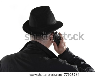 Man with hat is talking on phone from behind - stock photo