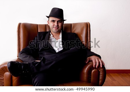 Man with hat seated on a chair - stock photo