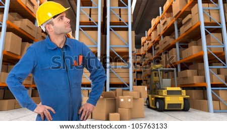 Man with helmet and blue overalls in a distribution warehouse - stock photo