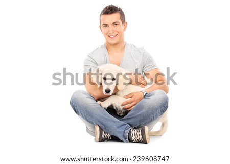 Man with his baby dog seated on floor isolated on white background - stock photo
