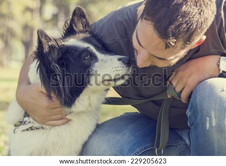 Man with his dog playing in the park - stock photo