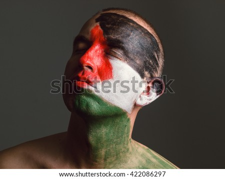 Man with his face painted with Palestinian flag. The man's eyes closed and looking sideways. - stock photo