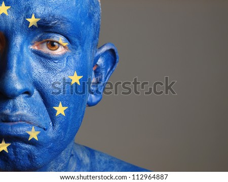 Man with his face painted with the flag of European Union. The man is sad and photographic composition leaves only half of the face. - stock photo