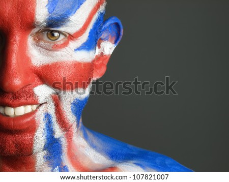 Man with his face painted with the flag of United Kingdom. The man is smiling and photographic composition leaves only half of the face. - stock photo