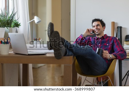 Man with his feet on the table talking on the phone - stock photo
