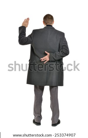 Man with his fingers crossed behind his back - stock photo