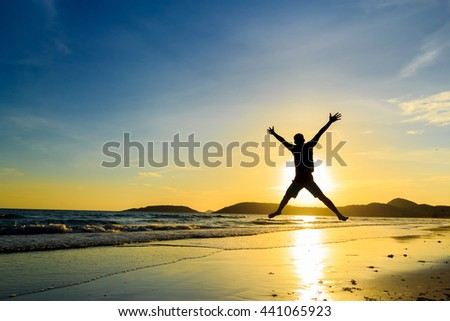 Man with his hands up at the sunset time on the beach - stock photo