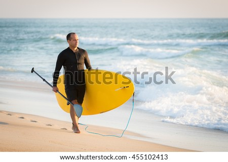 man with his paddle board on the beach at sunset. - stock photo