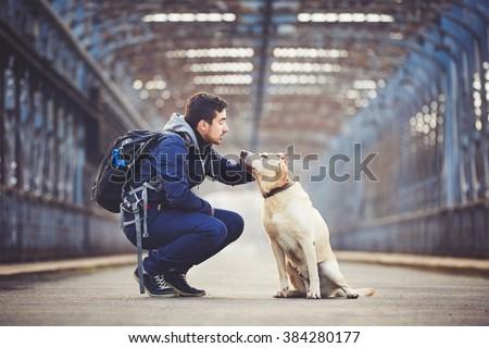 Man with his yellow labrador retriever on the old bridge - stock photo