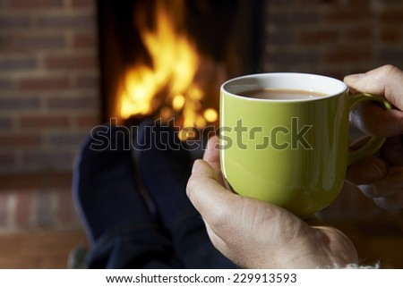 Man With Hot Drink Relaxing By Fire - stock photo
